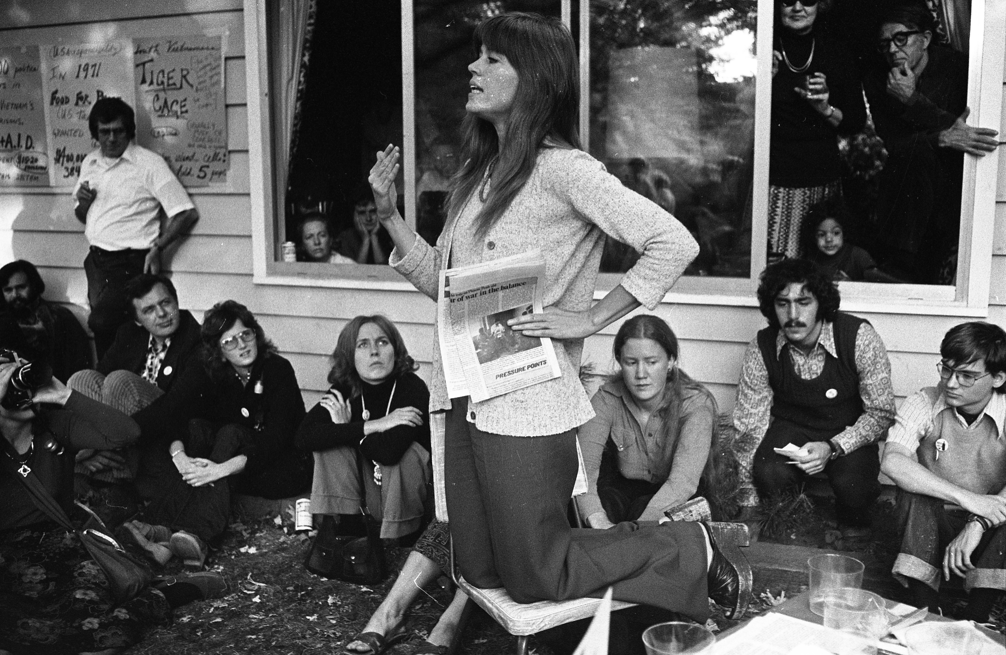 Jane Fonda Kneeling On Chair To Address Crowd At Dr. Edward Pierce's House For Fundraiser, October 1974 image