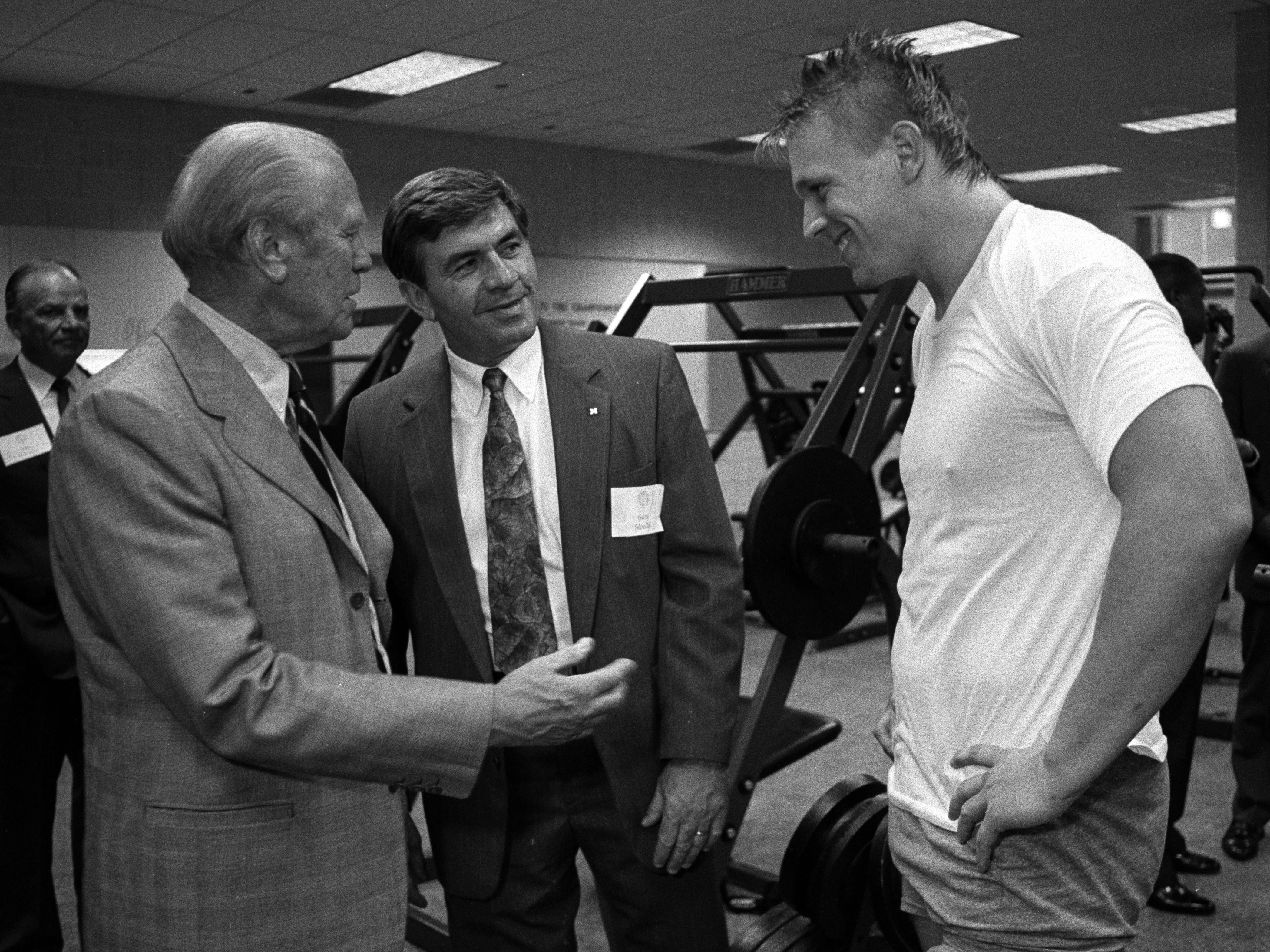 Gerald Ford and Coach Gary Moeller with a member of the Michigan Team in Weight Room, At the Opening of Schembechler Hall, June 1991 image