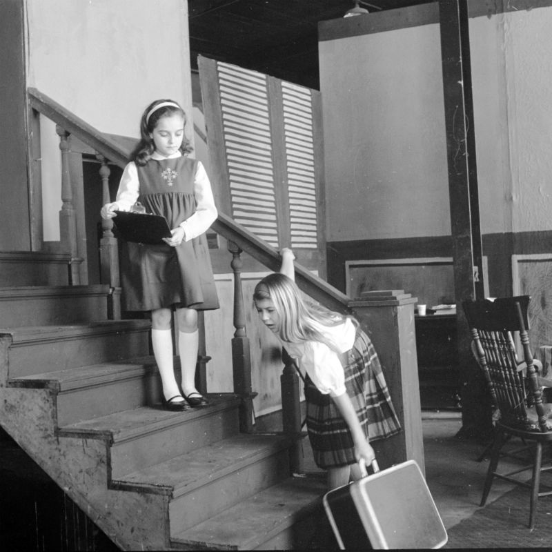Nine-year-old Rosemary Feit, on the stairs, watches 10-year-old Molly Marie Rae practice a scene from the Civic Theatre production of The Miracle Worker, 1964